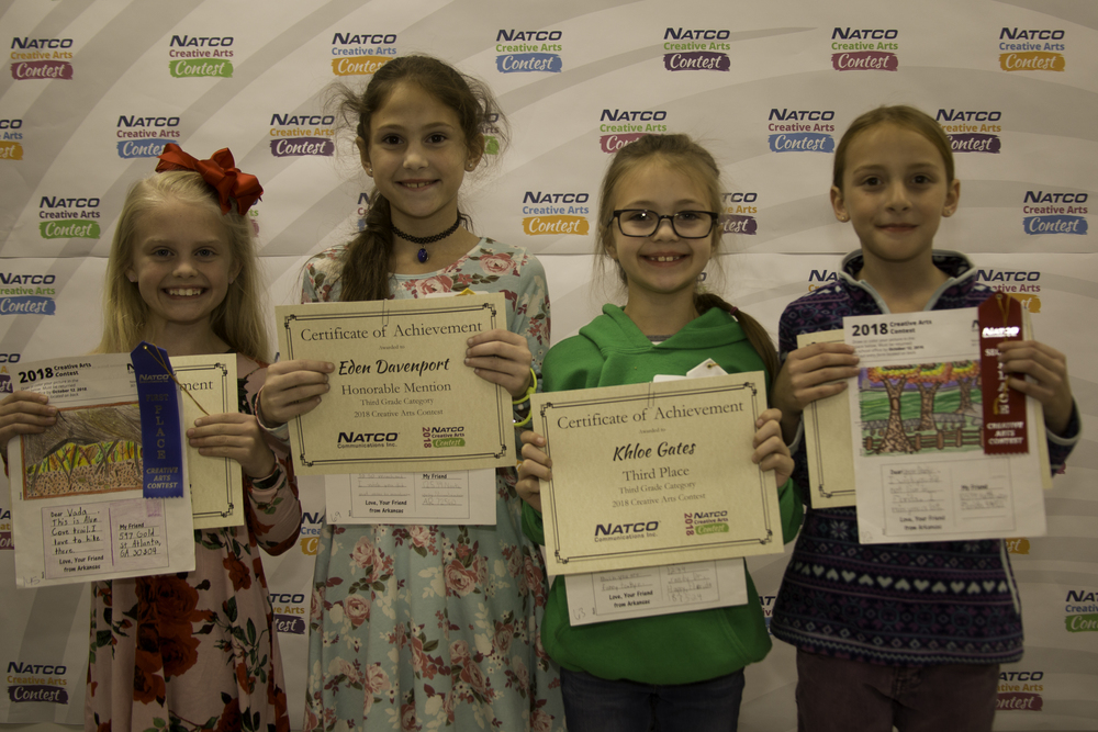 4 children holding award certificates