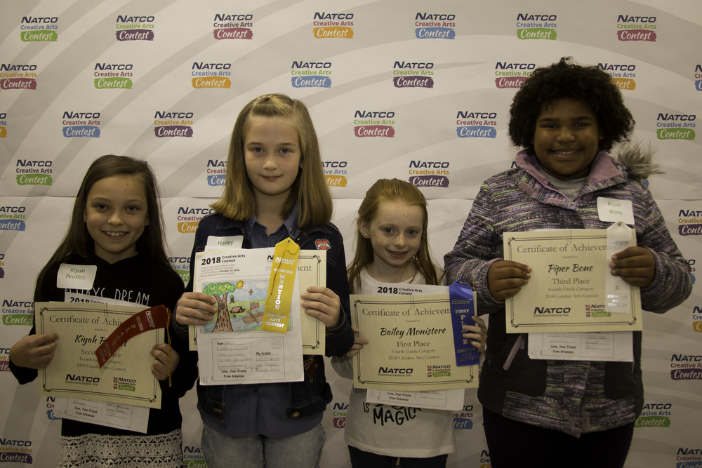 Group of 4 children holding certificates from natco