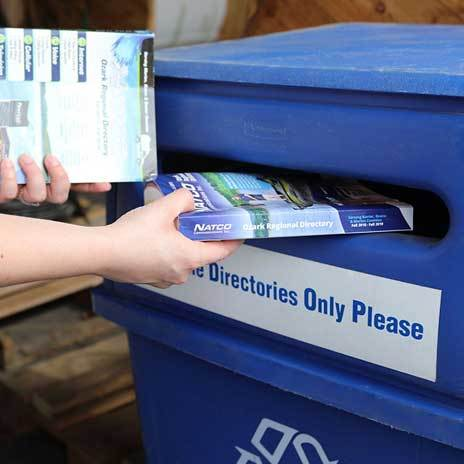 Person placing old phone books into recycling bin