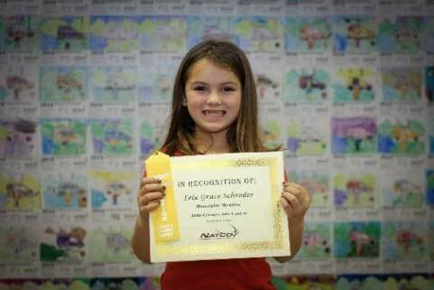 Child holding award certificate